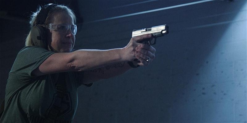 Woman shooting a pistol in an indoor range