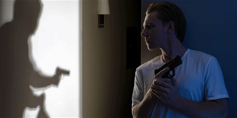 man with gun behind a wall