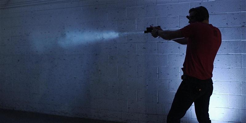 man shooting gun in low light conditions